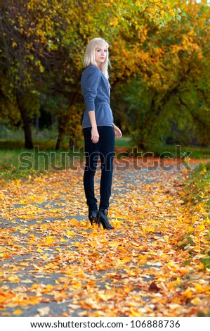 Young beautiful girl walking in autumn park