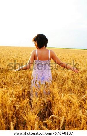 Young beautiful girl walking in the cornfield - stock photo