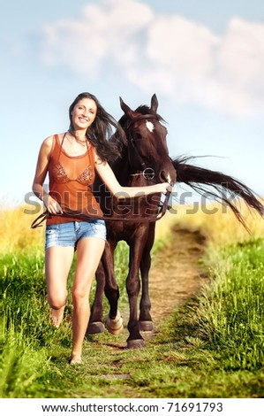 Young beautiful girl walking with a horse on the field - stock photo