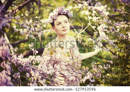 Young beautiful girl wearing wreath in the garden among a spring blossom. - stock photo
