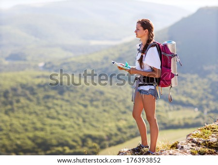 Young, beautiful girl with a backpack on her back, studying a map while standing on the plateau. In the background, green meadows and majestic mountains. - stock photo