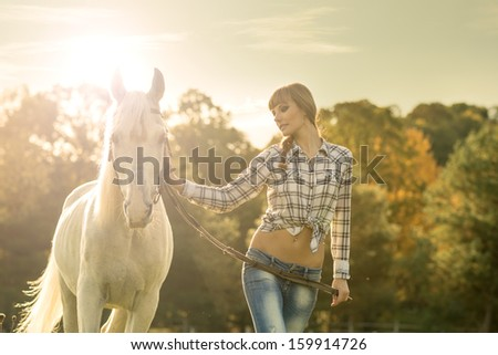 Young beautiful girl with a horse on the dry field