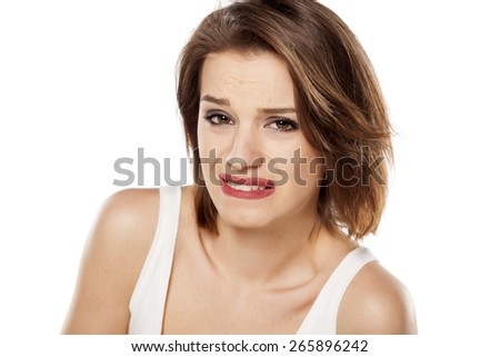 young beautiful girl with a painful gesture on her face - stock photo