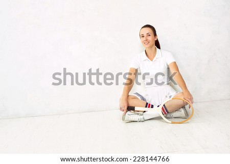 Young beautiful girl with a tennis racket in and in sportswear sitting on a white floor against a white textured wall. - stock photo