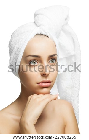Young beautiful girl with a towel on his head after a shower touching her face. Perfect clean skin.  Isolated on a white background - stock photo