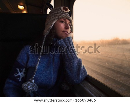 Young beautiful girl with a woolen hat and a jumper travels by train looking through the window towards the shining golden morning light - stock photo