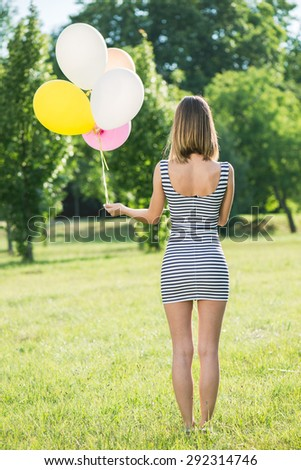 young beautiful girl with baloons posing outdoor - stock photo