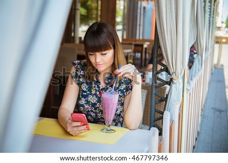 Young beautiful girl with brown hair sitting in a cafe and drinking berry smoothies, watching at mobile phone and reading