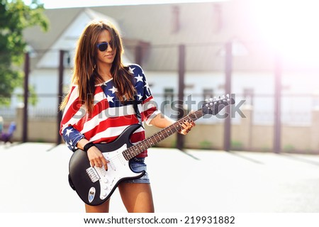 Young beautiful girl with electric guitar. Outdoor fashion portrait  - stock photo