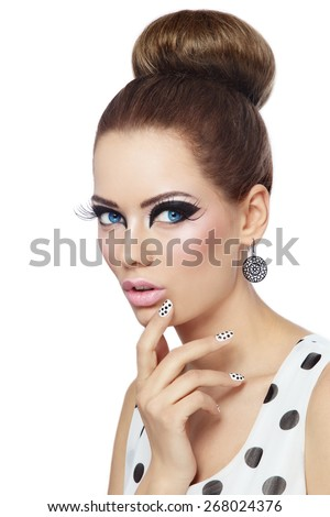 Young beautiful girl with fancy cat eyes and polka dot manicure over white background - stock photo