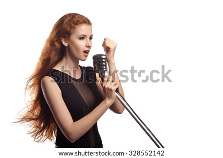 Young beautiful girl with flowing red hair singing into retro microphone.