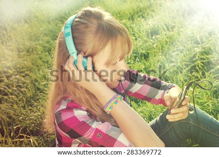 young beautiful girl with headphones on ears listening music in smartphone on the meadow in vintage style - stock photo