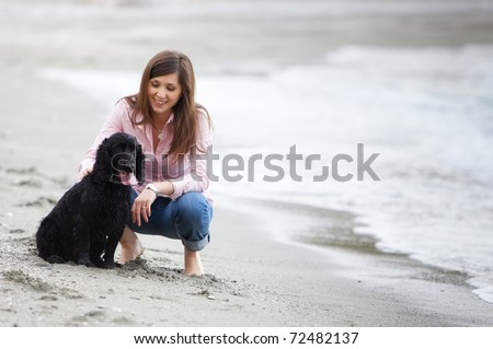 Young beautiful girl with her dog in the beach - stock photo