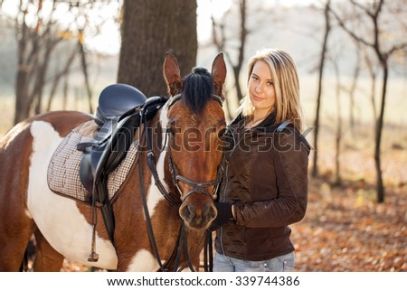 Young beautiful girl with horse in autumn sunset