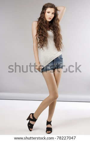 young beautiful girl with long curly hair wearing mini short jeans and posing - stock photo