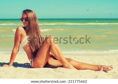 Young beautiful girl with long hair in swimsuit at the beach - stock photo