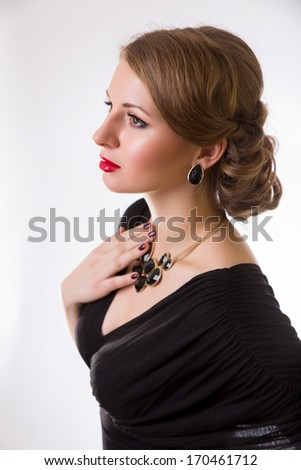 young beautiful girl with make-up and hairstyle in black dress and big jewelry