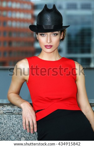 Young beautiful girl with perfect make-up, red lips, wearing a black hat