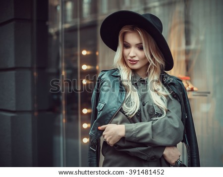 Young beautiful girl with perfect make-up, red lips, wearing a black  hat and leather coat, green shirt, posing near glass wall of the shopping center. - stock photo