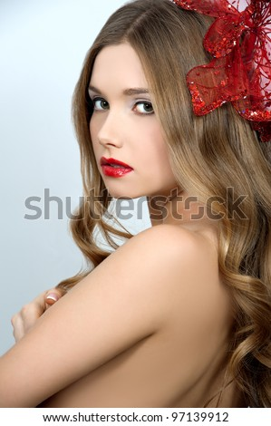 young beautiful girl with red flower in hair - stock photo