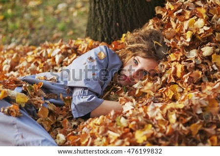 Young beautiful girl with sad eyes, dressed in a light blue cloak, lying on a pile of autumn leaves. She looks thoughtfully at the camera.