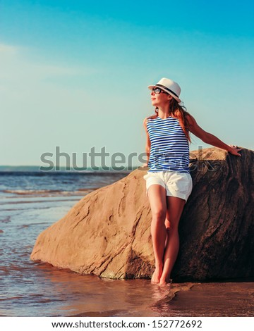 Young beautiful girl with sunglasses resting on the sea. - stock photo