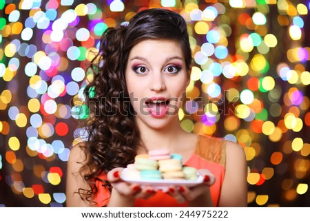 Young beautiful girl with tasty macaroon on bright background - stock photo
