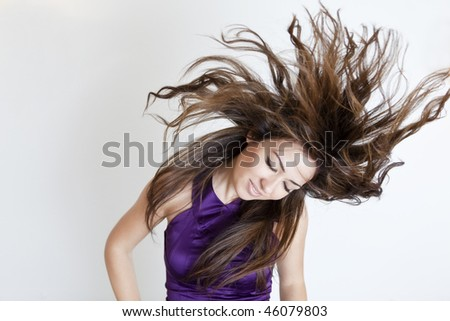Young beautiful girl with windy hair over white background. - stock photo