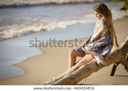 Young beautiful girl woman enjoying sunset at stormy sea