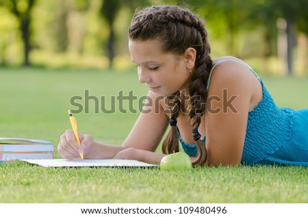 Young beautiful girl writing into her notebook in the park - stock photo
