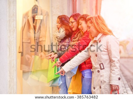 Young beautiful girlfriends looking shop windows city - Best friends having fun doing shopping in urban contest - People enjoying life moments - Focus on first girl on right - Artificial sunlight - stock photo