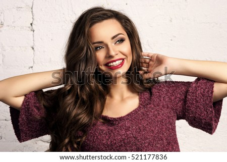 Young beautiful gorgeous female model in blue jeans and purple pullover posing against white brick wall. Stunning glamorous happy joyful smiling girl with long curly hair