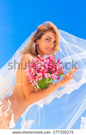young beautiful happy bride in white bikini holding flower bouquet on tropical sky and beach background