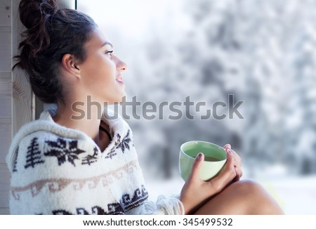 Young beautiful happy brunette woman drinking cup of coffee wearing knitted nordic print poncho sitting home by the window. Blurred winter snow tree background - stock photo