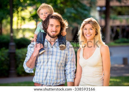 Young beautiful happy family at the park - stock photo