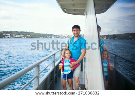 Young beautiful happy family girl and dad enjoying cruise on boat on background of Bosphorus channel in Istanbul Turkey, girl drinking orange juice - stock photo