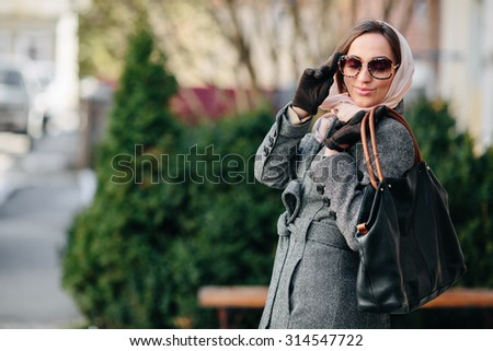 young beautiful happy girl in a coat posing at the park - stock photo