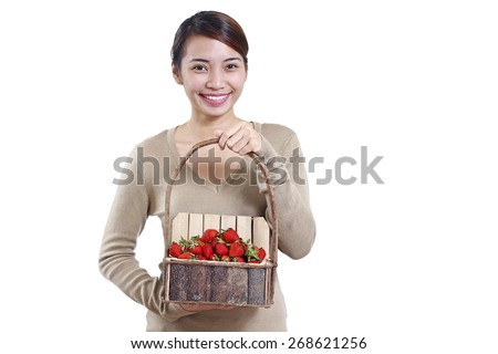Young beautiful happy lady with a basket of strawberries. Isolated in white background. High key.