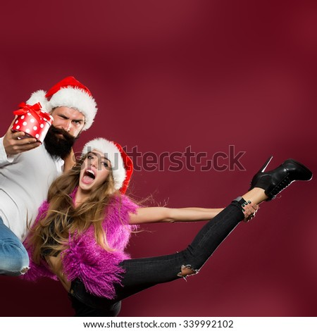Young beautiful happy new year couple of man with long beard with present box and woman in red santa christmas hat with fur in studio on purple background copy space, square picture - stock photo