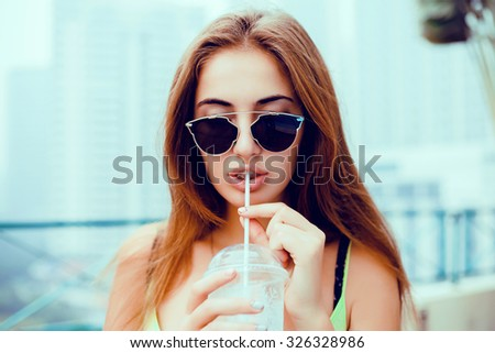 young beautiful happy stylish hipster girl,cocktail,smoozy drink,cold juice,smile and laughing,fashionable sunglasses,cool accessories, purse,amazed, vintage style,street background, hair, wind - stock photo