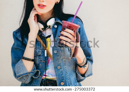 young beautiful happy stylish hipster girl, cocktail, smoozy drink, denim jacket, smiling, fashion, teen, cool accessories, purse, hat, sunglasses, vintage style, wall background, headphones, close up - stock photo
