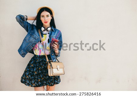 young beautiful happy stylish hipster girl, cocktail, smoozy drink, denim jacket, smiling, fashion, teen, cool accessories, purse, hat, sunglasses, amazed, vintage style outfit, wall background - stock photo