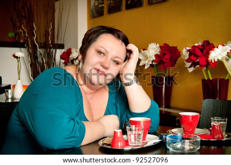 Young beautiful happy woman in a cafe - stock photo