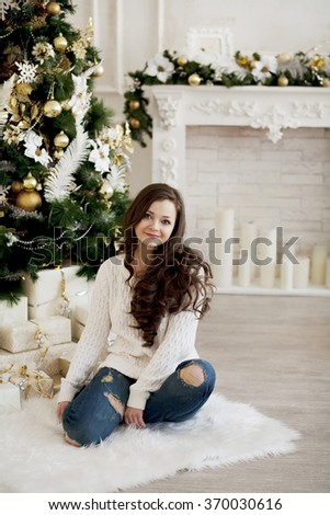 Young beautiful happy woman in sweater and blue jeans sitting on floor near christmas tree - stock photo