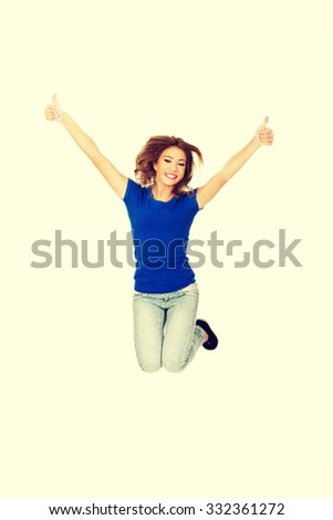 Young beautiful happy woman jumping with thumbs up. - stock photo