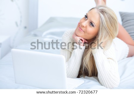 Young beautiful happy woman lying on the bed with laptop
