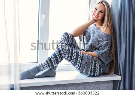 Young beautiful happy woman wearing knitted nordic print clothes sitting home by the window.  - stock photo