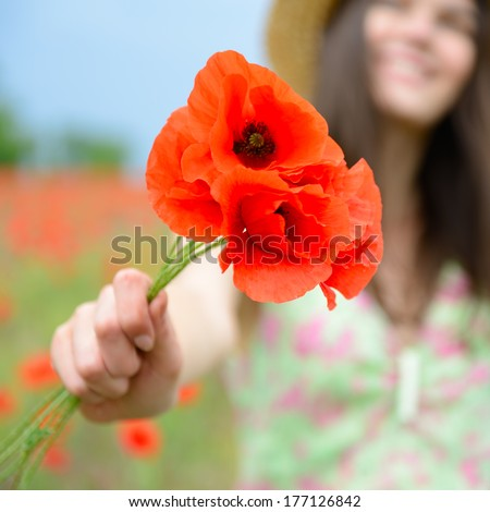 Young beautiful happy woman with bunch of poppy on field, summer outdoor. - stock photo