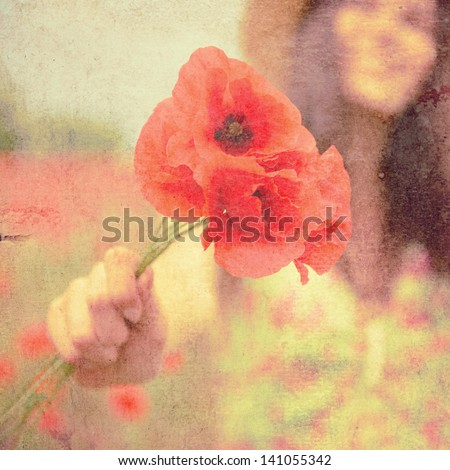 Young beautiful happy woman with bunch of poppy on field, summer outdoor. Vintage paper stylization, toned and texture added. - stock photo