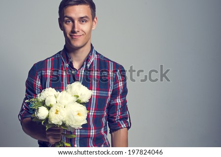 Young beautiful headsome attractive enamored man casual stule with flowers - stock photo